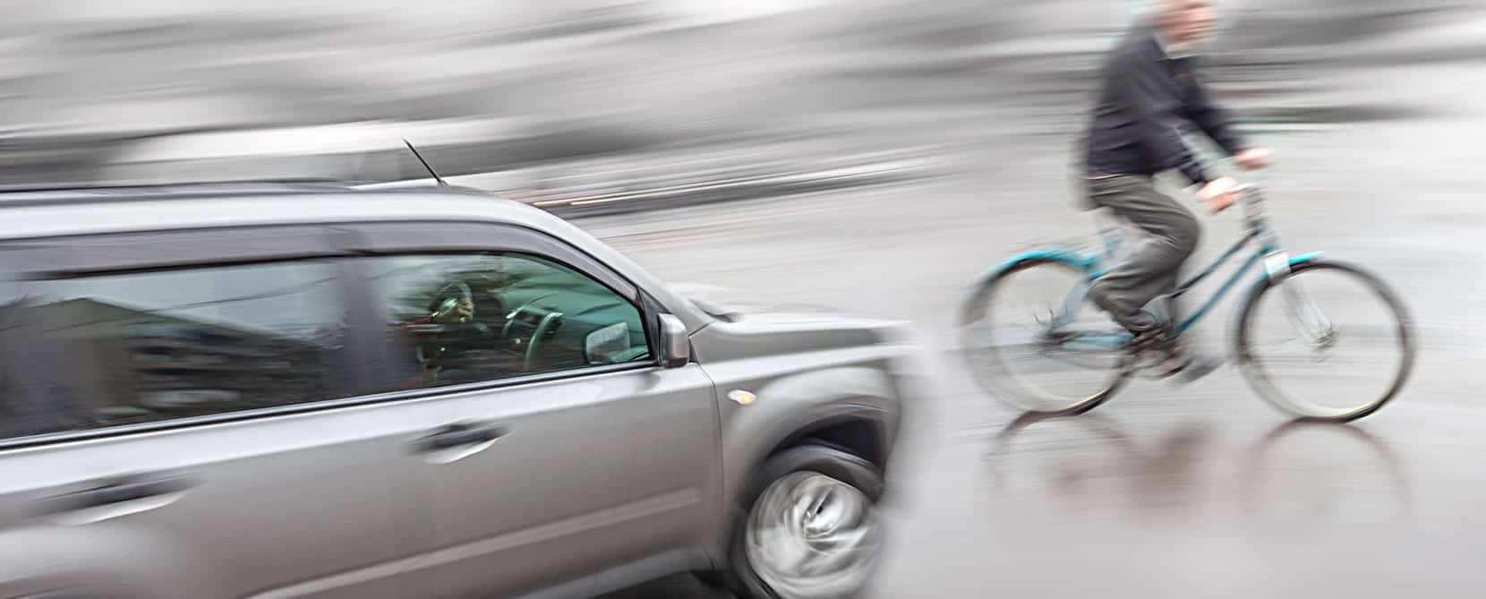 ' Man on bicycle about to get into a bicycle accident with an oncoming car '